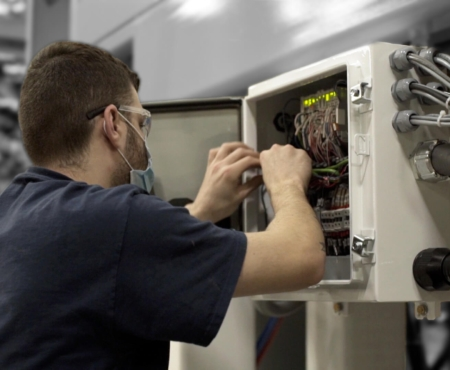 electrician testing a machine as part of solution design and parts and maintenance
