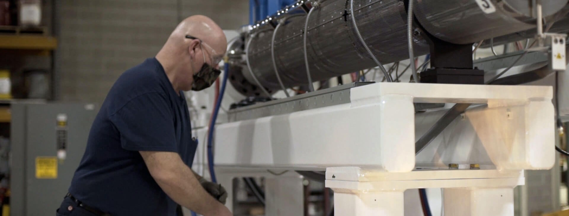 lifecycle management includes maintenance like this Graham employee working on an extruder