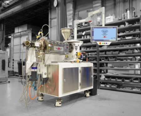 modular extruder shown in white and stainless steel in a factory setting
