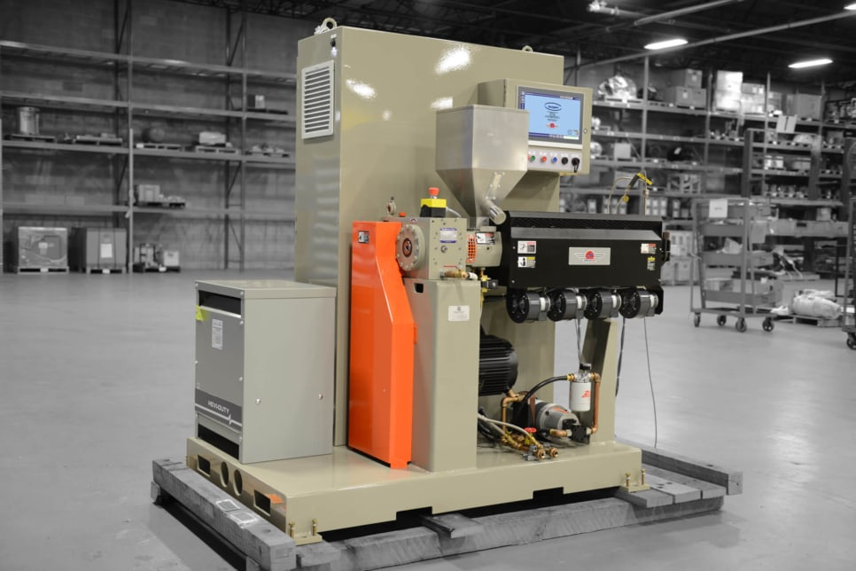Ultra extruder pictured in grey-brown in a factory setting.