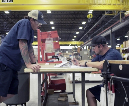 Two graham engineering people working at a table on the factory floor