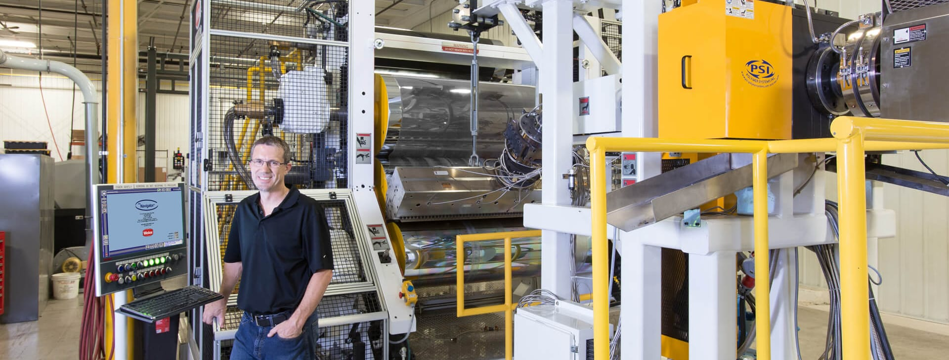 man standing in front of his Graham Extrusion equipment for parts and maintenance services photo